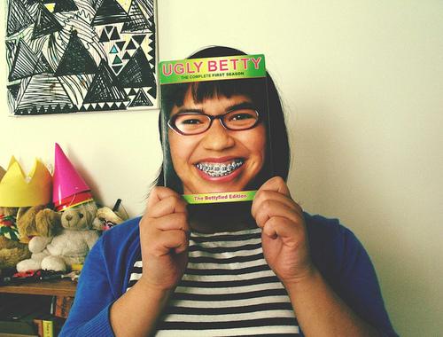 menina com a revista com capa de Uggly Betty fazendo como se fosse o seu rosto